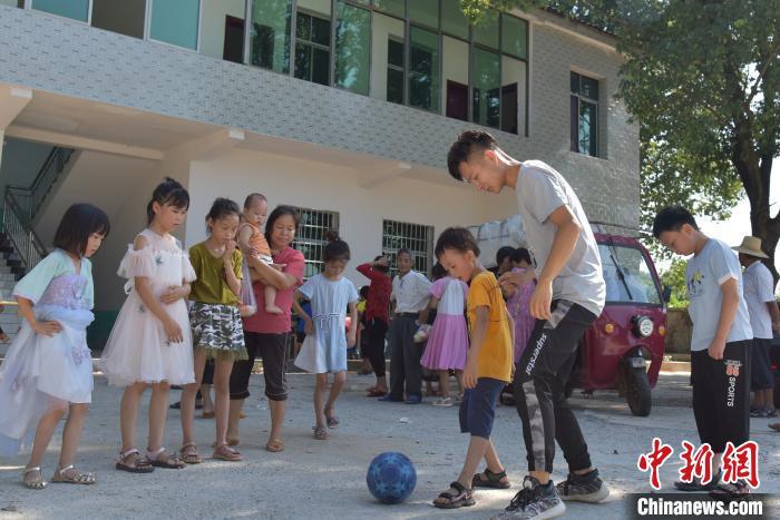 志愿者和小学生一起踢球。 肖亚辉 摄